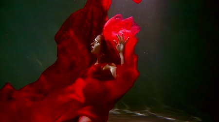 nadador : young woman with long dark hair in a red dress swimming under water like in a fairy tale Stock Footage