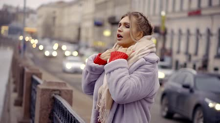 moda : Woman stands by the river in the winter city.