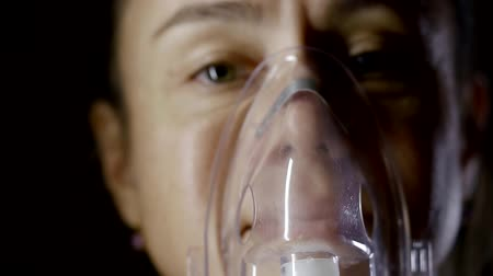 asthma : Portrait of a woman breathing through the oxygen mask in complete dark.