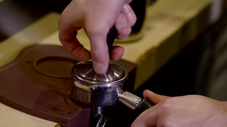 coffee press : barista is loading ground coffee in a coffee machine, clamping by press, close-up of his hands