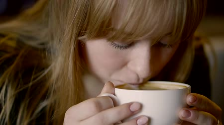 vendég : young pretty woman is drinking coffee from white cup, then rising eyes in camera and smiling Stock mozgókép