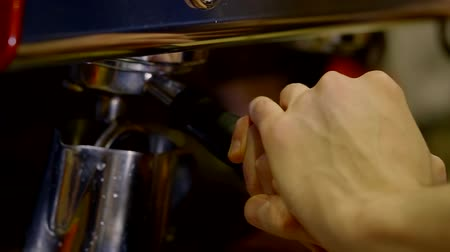латте : Close up shot of a barista making coffee in coffeemaker indoor.