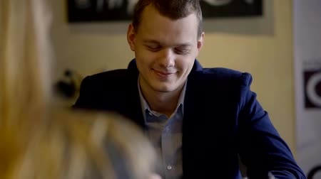 kifejező pozitivitás : Portrait of a handsome young guy wearing suit on a date with a girl in comfy cafe. Stock mozgókép