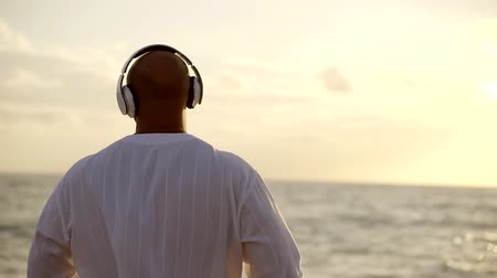 vigorous : Guy is listening to music standing on the beach Stock Footage