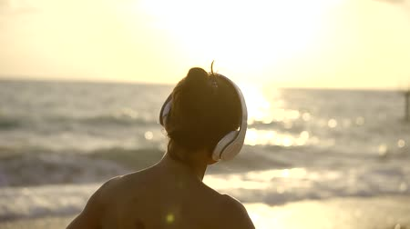 ouvir : Girl is chilling on the beach with headphones Stock Footage