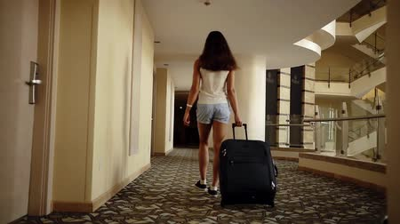 arriving : Woman with a baggage is going across the hall in hotel. Stock Footage