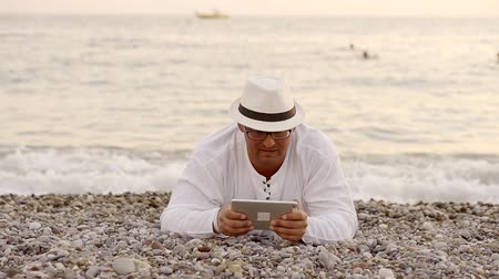 типы : Well-build man lies on a beach with a tablet