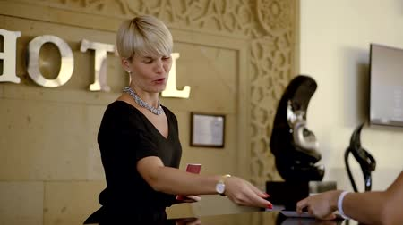 liga : Receptionist greets toursit in the hotel.