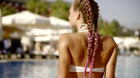 roupa de banho : Cute girl with a pink curls sits by the pool.