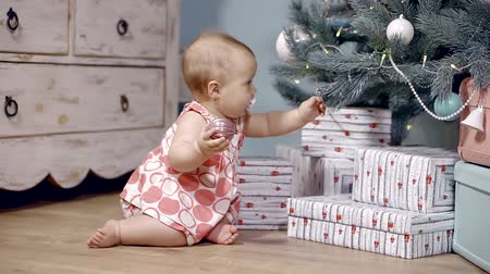 elves : nine months baby girl playing with a Christmas toy and a Christmas tree tries to hang the ball on a branch. sucking a pacifier in his mouth Stock Footage