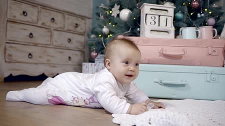 elf : child born nine months lying on his stomach on the floor in the room with festive d cor. she smiles and waves at feet