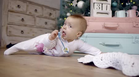 soon : girl kid in white overalls crawling on the floor in a Christmas interior with a pacifier in his hands Stock Footage