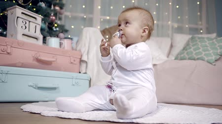 soon : cute infant baby girl in a white jumpsuit sitting on the floor on the Christmas tree. itchy gums will soon be teeth trying to chew on a pacifier
