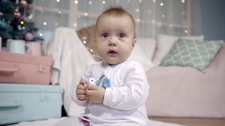 ниппель : baby is looking big dark eyes at the camera and holding the nipple with little fingers. sitting on the floor in festive interior