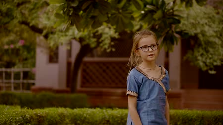 schooler : calm little girl is wearing glasses and blue tunic is walking in a garden in sunny day