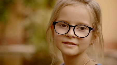 schooler : cheerful little european girl is wearing glasses, looking at a camera, is outdoor in garden