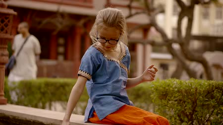schooler : little european girl is wearing traditional indian clothes is sitting on a pond in a garden of hindu temple Stock Footage
