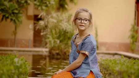 avlu : cute little blonde girl is wearing bright indian dress is sitting near water in garden in courtyard of temple Stok Video
