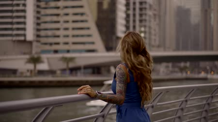 see off : romantic blonde with long wavy hair is standing in embankment in middle of big city and waving hand Stock Footage