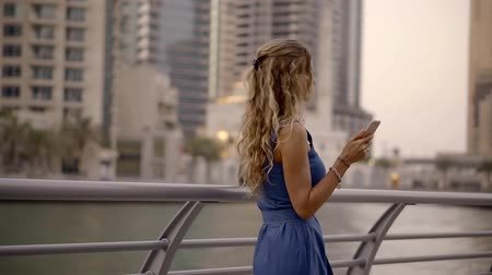 pinup : romantic young woman with wavy hair is wearing blue dress is waiting for someone on evening embankment