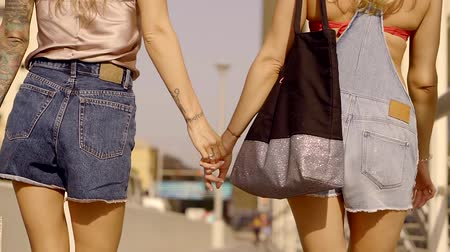 bum : lesbians blondes in love are walking on a sunny street holding hands, back view of their butts