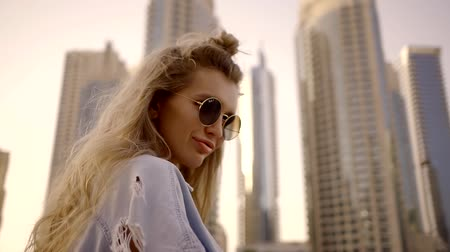 gesticulando : stylish modern blonde girl is wearing trendy sunglasses is standing on background of skyscrapers in modern city