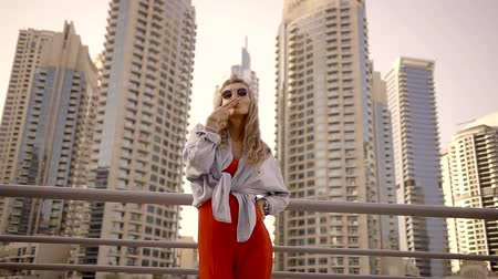 imaginário : extravagant woman is standing near skyscrapers , simulating smoking and pistol shooting