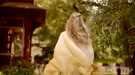 beckoning : cheerful attractive blonde girl is wearing romantic light dress with shawl, running in summer park