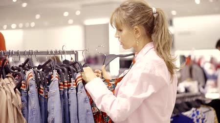 продавщица : Charming blonde woman picking new clothes in a shopping centre alone.