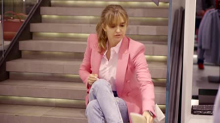 high heel shoe : Pretty young woman sits on a stairs in a shopping mall and puts on a new pair of low heels shoes. Stock Footage