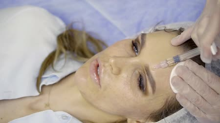 perforation : Portrait of a woman lying on a surgical table during cosmetic operation. Stock Footage