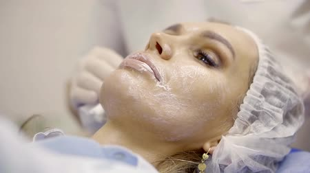 perforation : Close up shot of a surgeon cleaning womans face from cream with wet wipes indoor. Stock Footage