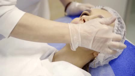 perforation : Close up shot of a surgeon applying special cream on patients face. Stock Footage