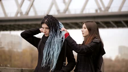 неформальный : girl is helping her friend with her long blue dreadlocks, fixing her hairstyle