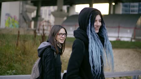 after school : two teenage girl is walking on a street in autumn day, one girl is having a dreadlocks on her head