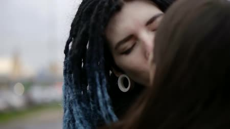 parte : two young lesbians girl are kissing on a street in daytime, one girl is having dreadlocks hairstyle Stock Footage