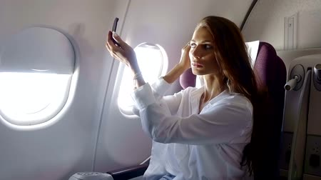 arrive : young pretty woman is applying cosmetic powder on her face, sitting on a seat in a modern airplane