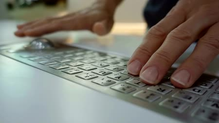 construído : humans hands are typing and using roller ball mouse, close-up shot of built-in keyboard and mouse Stock Footage