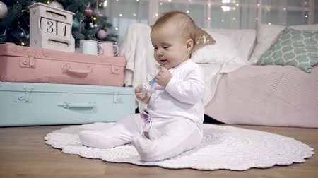 ниппель : baby is sitting on a carpet on a floor in a nursery in a Christmas and new year holidays, looking on a pacifier