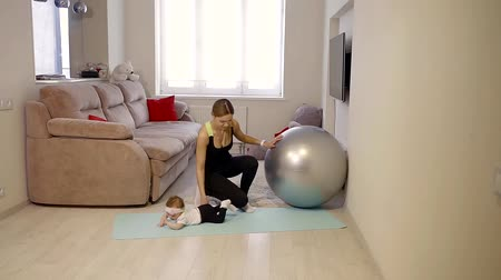 склон : Fitness mom trains at home in the living room on the fitball and plays with her newborn daughter