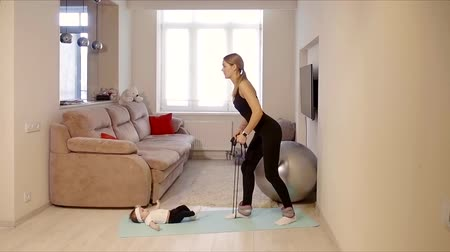 nursing : woman is engaged in sports in her apartment with a child who lies on the floor Stock Footage