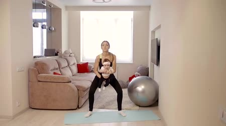 néz : a young woman doing sit-ups holding a child, she is at home in the living room