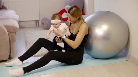 crouch : an adult woman resting after a workout, she is holding her daughter in her arms