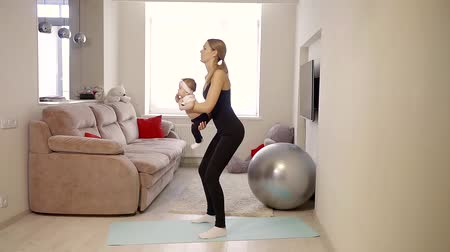 crouch : woman strengthens the buttocks muscles during the home exercise, she hold baby