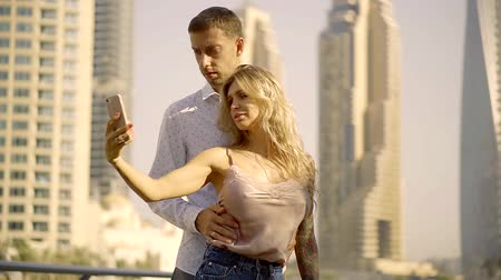 resimlerinde : man and sexy woman take a photo on the skyscrapers background Stok Video