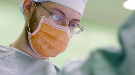 eye mask : face of young surgeon wearing correcting glasses, during work in an operating room, close-up Stock Footage