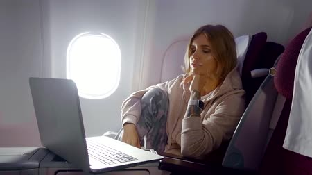 lengthy : bored and tired woman is on a cabin of plane, during a fly, looking on a screen of her laptop