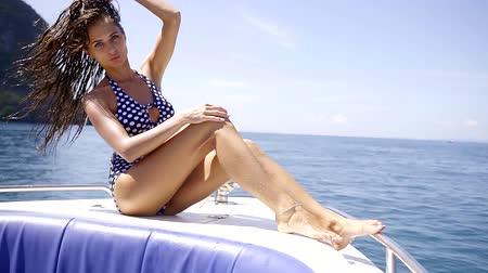 opalenizna : woman is wearing trendy black and white swimsuit is sitting on a yacht in a sea near picturesque islands Wideo
