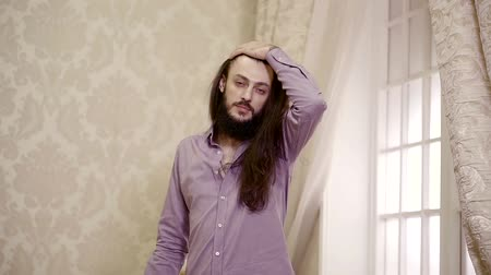 sensuous : attractive man with long dark hair is walking on a living room near large window, moving to camera