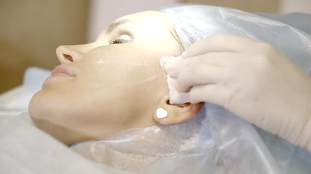 mezoterapia : cosmetologist is doing injection in face skin of adult woman, lying in a treatment hall